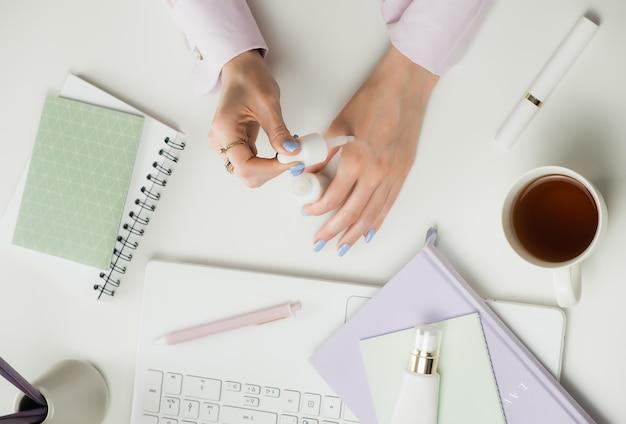 Weibliche beauty-bloggerin oder beraterin. fernarbeit von zu hause aus. freiberufler laptop, tasse kaffee. online-shopping-kosmetik. office white desktop, flat lay, mock-up und copyspace.