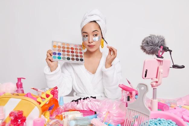 Weibliche beauty-bloggerin testet kosmetik zu hause hält lidschatten-palette teilt eindrücke mit followern gibt empfehlungen, wie man make-up-filme auf der smartphone-webcam für die zuschauer verarbeitet.
