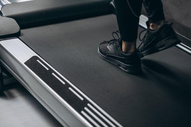Weibliche beine auf der laufbahn im fitnessstudio