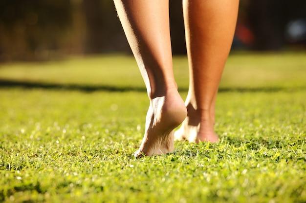 Weibliche beine auf einem gras an einem sonnigen sommer- oder frühlingstag