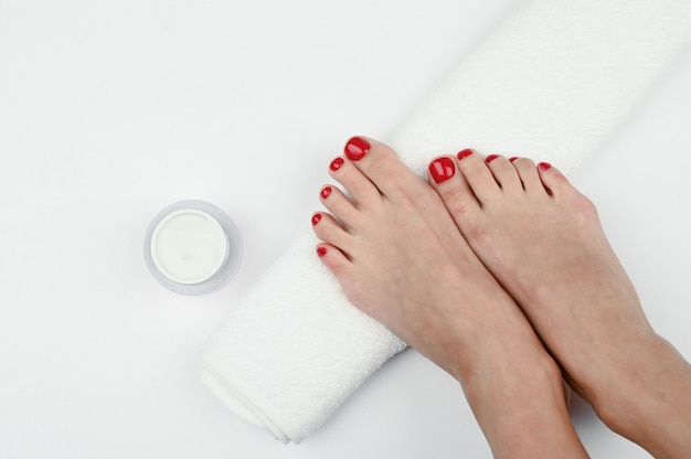 Weibliche beine auf einem weißen handtuch