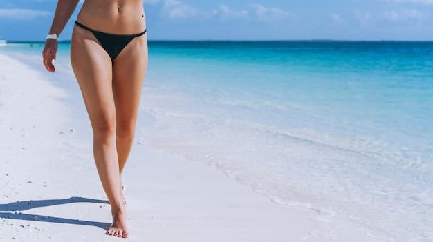 Weibliche beine, die auf sand durch den ozean gehen