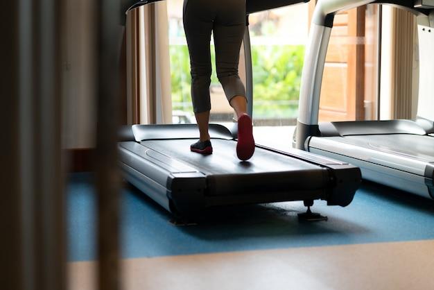 Weibliche beine, die auf tretmühle in der turnhalle gehen und laufen. cardio-training trainieren