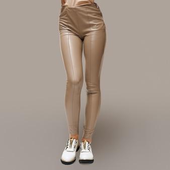 Weibliche beine in beige kunstlederhose und grobe stiefel mit gerillter laufsohle