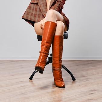Weibliche beine in braunen stiefeln sitzen auf stuhl