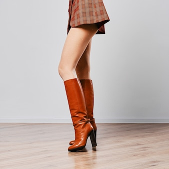 Weibliche beine in braunen stiefeln und weißen strumpfhosen mit punktmuster