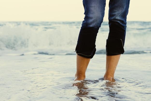 Weibliche beine in den jeans, die im meerwasser auf dem hintergrund einer brechenden welle stehen