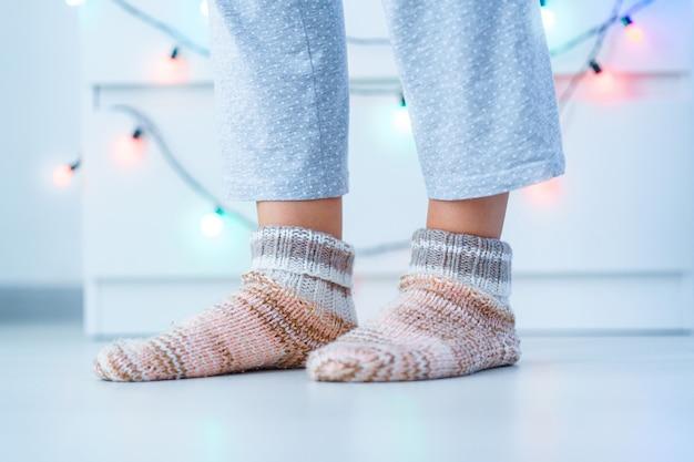 Weibliche beine in den warmen gestrickten weichen gemütlichen socken in der winterzeit zu hause.