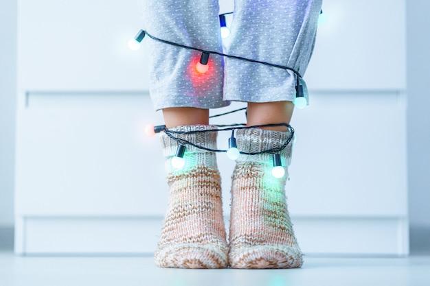 Weibliche beine in den warmen gestrickten weichen gemütlichen weihnachtssocken und -girlande mit belichteten lichtern in der winterzeit zu hause.