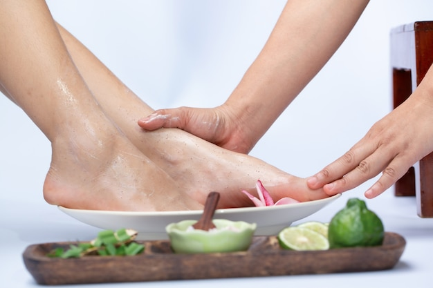 Weibliche beine in der wasserdekoration die blumen frau, die eine pedikürebehandlung an einem badekurort oder an einem schönheitssalon mit dem pediküristmassieren hat