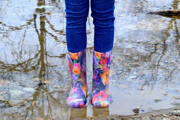 Weibliche beine in floralen gummistiefeln in einer pfütze mit reflexion