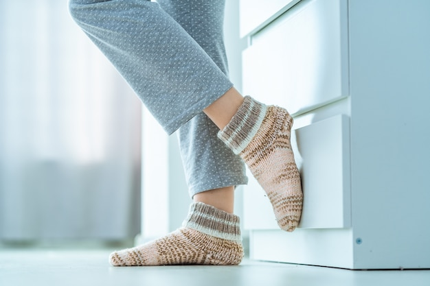 Weibliche beine in kuscheligen weichen, bequemen, gestrickten wintersocken zu hause