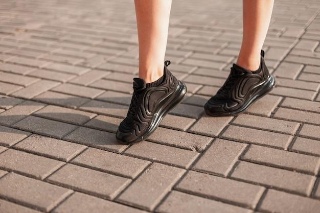 Weibliche beine in modischen schwarzen sportlichen turnschuhen. trendy mädchen geht durch die stadt an einem sonnigen sommertag. nahaufnahme der weiblichen beine in den stilvollen schuhen.