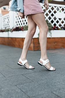 Weibliche beine in modischen sommerschuhen und einem rock in der stadt