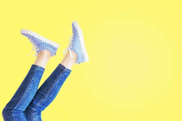 Weibliche beine in pose auf gelbem hintergrund. frauenfüße in jeans und gestreiften turnschuhen mit kopierraum