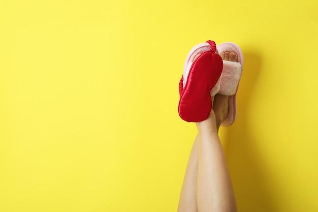 Weibliche beine in rosa hausschuhen mit schlafmaske auf gelb