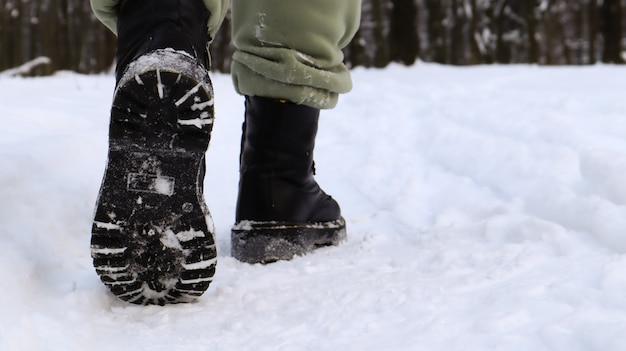 Weibliche beine in schwarzen stiefeln, winterspaziergang im schnee. aktive frau, die im winterwald von der kamera weggeht. konzentriere dich auf deine beine. schönes weißes winterwetter mit neuschnee.