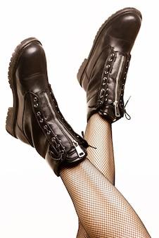 Weibliche beine in sexy strumpfhosen und schwarzen armeestiefeln