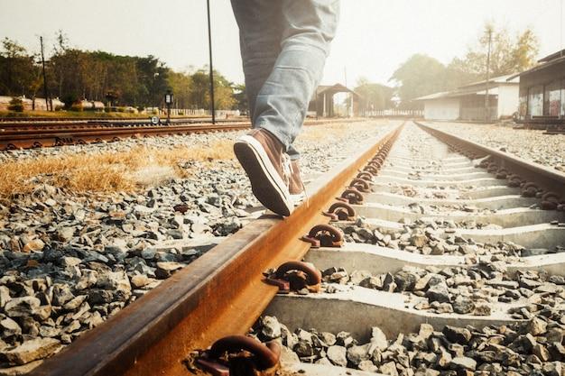 Weibliche beine in sneakers auf der schiene der eisenbahn.