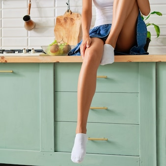 Weibliche beine in socken auf küchentisch