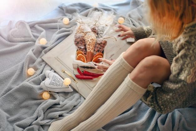 Weibliche beine in socken weihnachtsschmuck mit lichtern mädchen paking weihnachtsgeschenke
