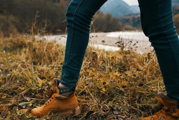 Weibliche beine in stiefeln und jeans auf natur im herbst in den bergen