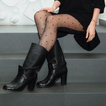Weibliche beine in strumpfhosen und stiefeln auf treppen