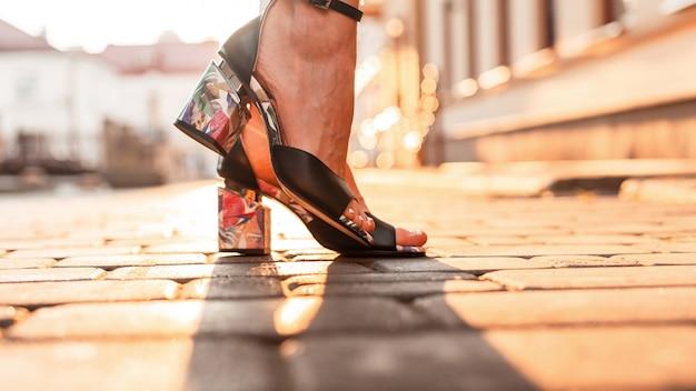 Weibliche beine in trendigen sommerschuhen mit palmenprint auf der straße bei sonnenuntergang