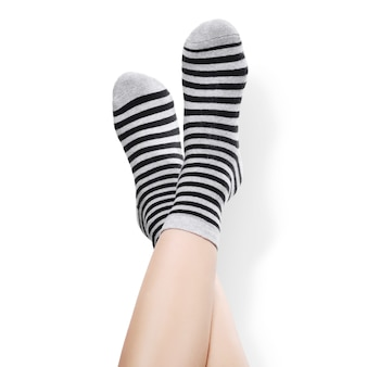 Weibliche beine in warmen gestreiften schwarzen und grauen socken auf weißem hintergrund angehoben.