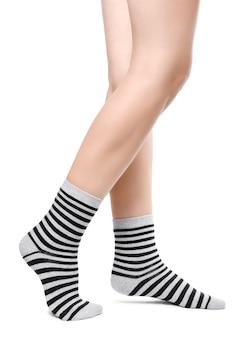 Weibliche beine in warmen gestreiften schwarzen und grauen socken isoliert auf weißem hintergrund.