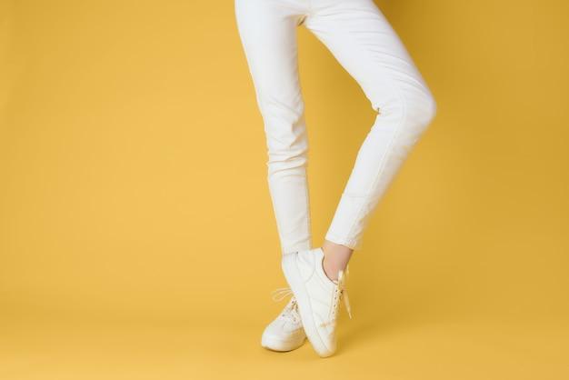 Weibliche beine in weißen hosen turnschuhen mode gelben hintergrund. foto in hoher qualität