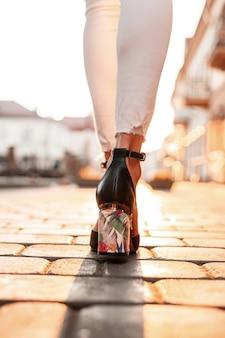 Weibliche beine in weißen jeans in eleganten ledersandalen spazieren bei sonnenuntergang durch die stadt. ansicht von oben