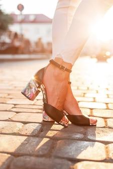 Weibliche beine in weißen modejeans in eleganten ledersandalen stehen bei sonnenuntergang in der stadt.nahaufnahme