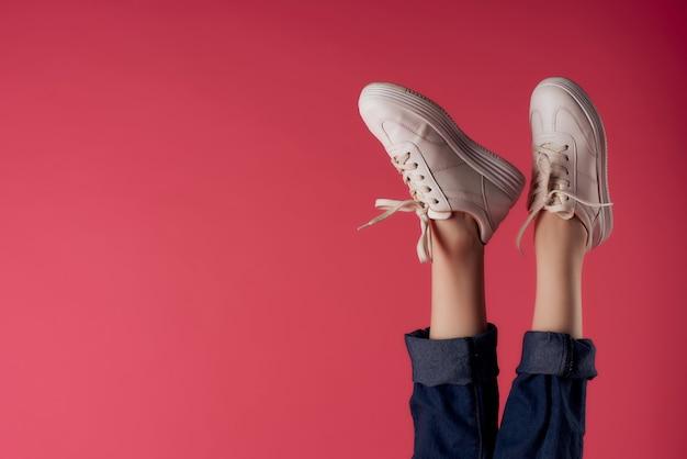Weibliche beine kopfüber in weißen turnschuhen rosa hintergrundmode background