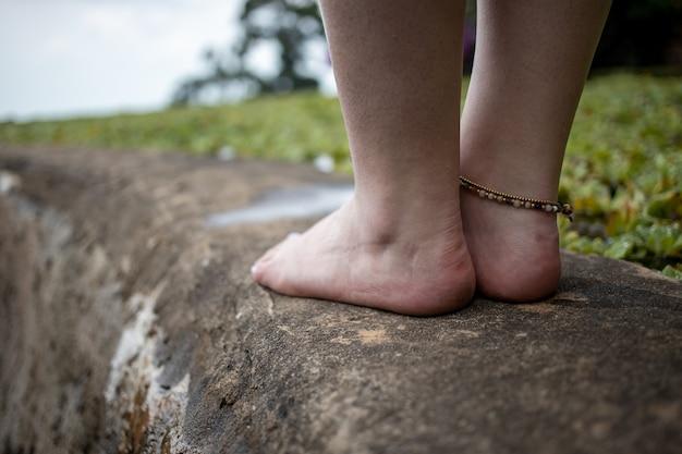 Weibliche beine mit armband am teichrand vor dem hintergrund einer naturlandschaft