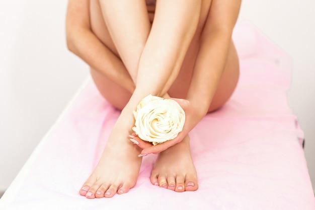 Weibliche beine mit einer weißen rose in den weiblichen händen, die auf einer couch in einem schönheits-spa sitzen