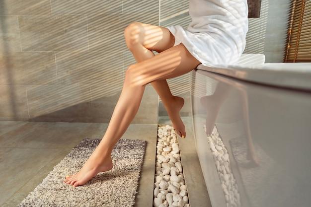 Weibliche beine mit gelbem nageldesign im badezimmer mit sonnenlicht