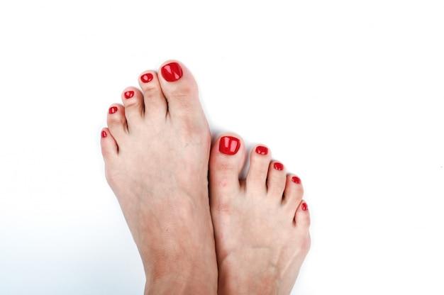 Weibliche beine mit rot lackierten nägeln. auf einem isolierten raum