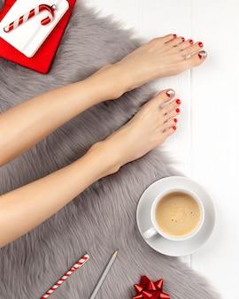 Weibliche beine mit roten nägeln und kaffeetasse auf grauer flauschiger decke. weihnachtsfeier-konzept.