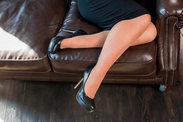 Weibliche beine mit schwarzen schuhen der hohen absätze arbeiten auf gemütlichem sofa