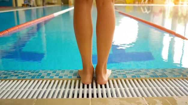 Weibliche beine stehen in der nähe des klaren wassers des swimmingpools, um im modernen fitnessstudio bei hellem licht in der nähe der rückseite zu trainieren