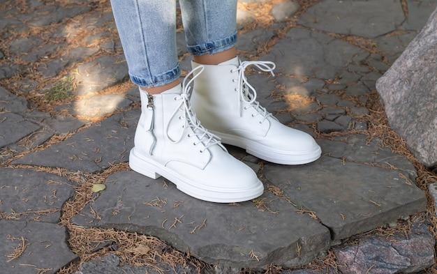 Weibliche beine tragen weiße modestiefel mit schnürsenkeln