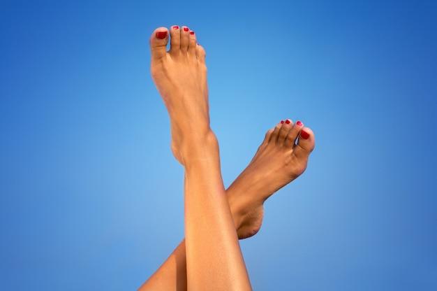 Weibliche beine über blauem hintergrund