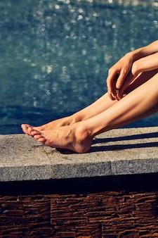 Weibliche beine und hände unter der sonne nahe dem wasser am schwülen heißen tag