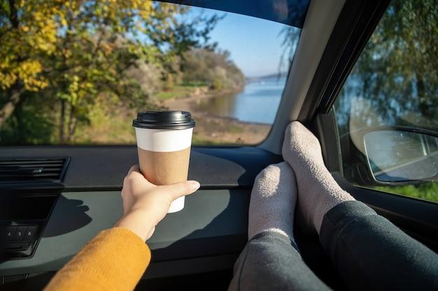 Weibliche beine und hand halten eine tasse kaffee in einem auto. naturlandschaft außerhalb des autos