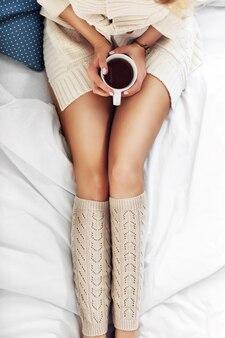 Weibliche beine und kaffee auf dem bett