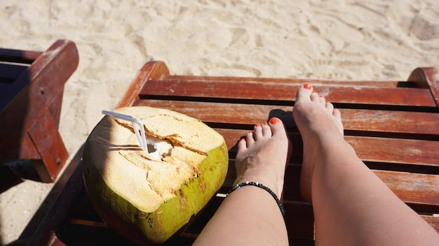 Weibliche beine und kokosnuss trinken am strand, reisen und entspannen