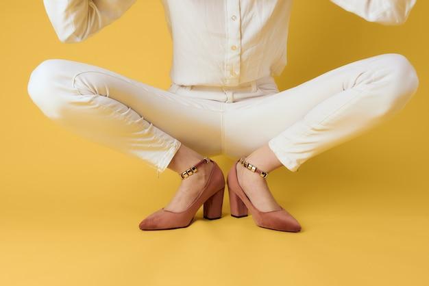 Weibliche beine weiße hosen modische kleidung schuhe luxus gelben hintergrund