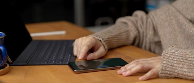 Weibliche berührung auf smartphone beim sitzen am arbeitsbereich mit digitaler tablette auf holztisch
