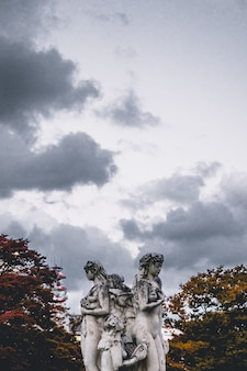 Weibliche betonstatue unter weißen wolken